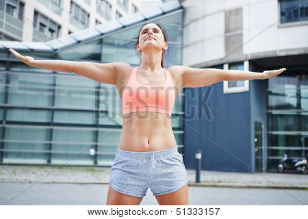 Sporty woman exercising to breathing freely in the city