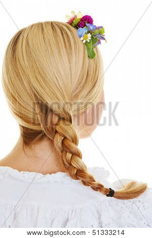 Traditional french plait with flowers in blonde female hair