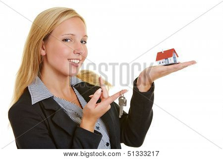 Happy business woman offering a small house and keys on her hand
