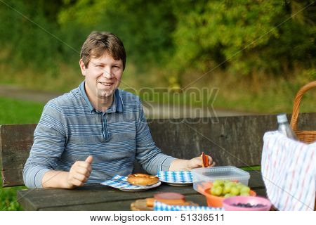Young Man Picnicking In The Park