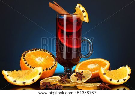 Fragrant mulled wine in glass with spices and oranges around on blue background