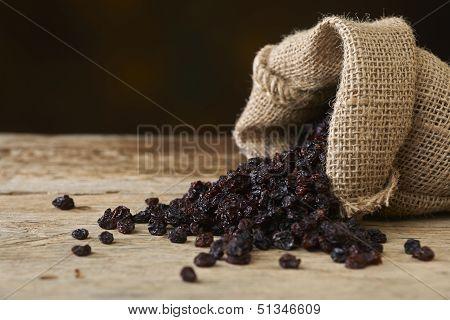 Black Raisins In Burlap Bag Over Wooden Table
