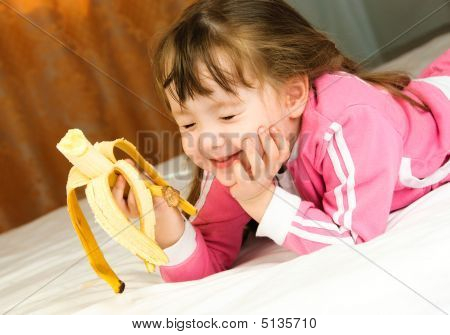 Little Girl Eating A Banana