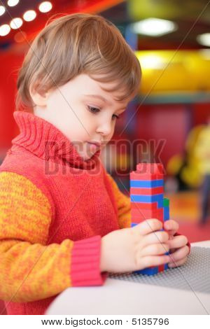 Little Girl Plays With Plastic Constructor In Kindergarten
