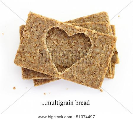 Stack of multigrain slices of bread, with cut out shape of heart, isolated on white