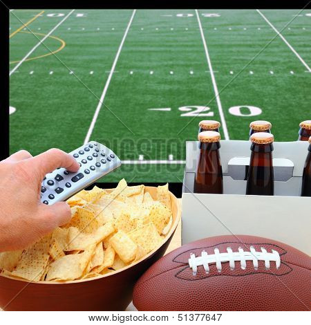 Closeup of a man's hand holding a TV remote with a bowl of chips and a six pack of beer with a football field on the television screen in the background. Square Format.