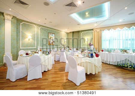 Hall with tables and chairs in a restaurant decorated for a wedding celebration, in place of pictures photo by the author.