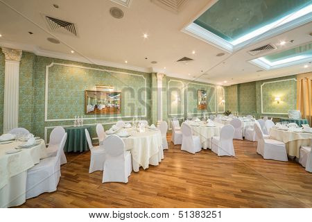 Beautiful hall with pictures and tables in a restaurant decorated for a wedding celebration,  in place of pictures photo by the author.
