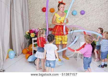 Five happy kids and facilitator play with long balloons at funny children party.