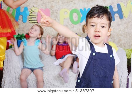 Happy little boy points his finger to side at funny children party. Inscription Happy Birthday on wall.