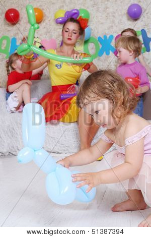 Four happy kids and facilitator make pets of long balloons at children party. Focus on girl with blue balloon. Inscription Happy Birthday on wall.