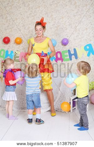 Three kids and facilitator play with balloons at funny children party. Inscription Happy Birthday on wall.
