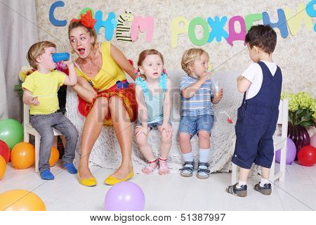Four little kids with juice and entertainer sit on sofa at funny children party.
