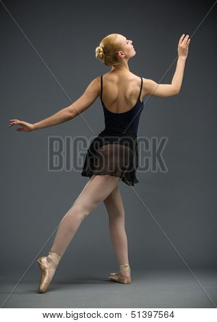 Backview of dancing ballerina, isolated on grey. Concept of elegant art and sportive hobby