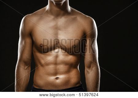 Close up of naked male's body, isolated on black