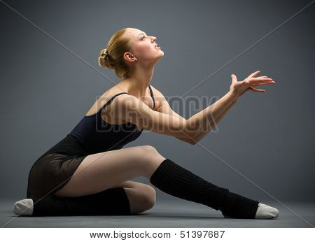 Dancing on the floor ballerina with palms up, isolated on grey. Concept of elegant art and sportive hobby