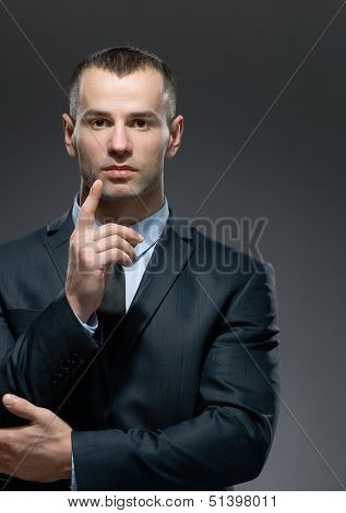 Portrait of making attention gesture businessman wears business suit and black tie