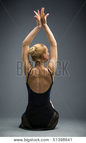 Backview of dancing on the floor ballerina with hands up, isolated on a white on grey. Concept of elegant art and sportive hobby