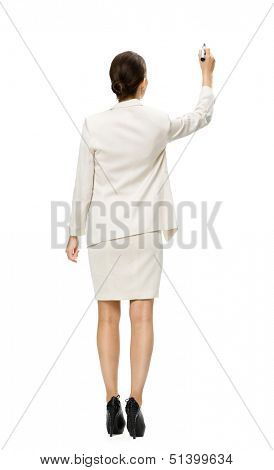 Full-length backview of businesswoman writing on imaginary screen with marker, isolated on white. Concept of leadership and success