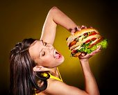 stock photo of high calorie foods  - Slim woman holding hamburger - JPG