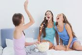foto of slumber party  - Friends messing around at slumber party at home on the bed - JPG