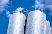 image of silos  - Metall silo with blue sky and clouds - JPG