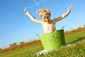 stock photo of hot-weather  - a happy young boy is playing outside in a small green wash basin and is splashing bubble water in the air on a summer day