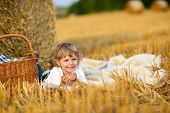 Little Boy Of 3 Years Picnicking On Yellow Hay Field In Summer