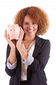 stock photo of brazilian money  - Young african american business woman holding a piggy bank isolated on white background  - JPG