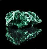 image of crystallography  - malachite mineral stone close up  with reflection on black surface background - JPG