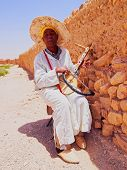 Man Playing Traditional Moroccan Instrument.