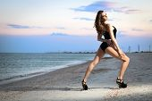 pic of leggy  - Attractive leggy brunette wearing black swimsuit posing on the beach - JPG