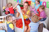 picture of dog birthday  - Five happy kids and facilitator make dogs of long balloons at children party - JPG
