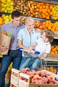 Happy family against shelves of fruits goes shopping. Father keeps a bag with fruits and son sits in