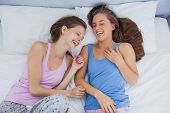 foto of slumber party  - Girls wearing pajamas lying in bed and laughing at slumber party - JPG