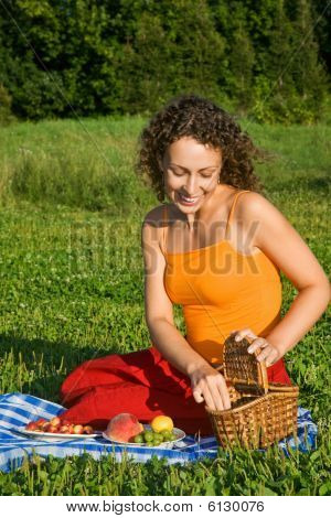 Young Women Will Get From Basket Fruits In Garden