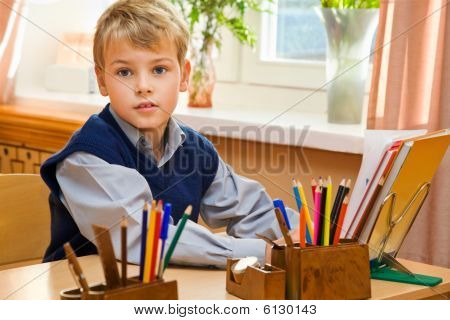 Young Schoolboy Packs Books Behind A School Desk