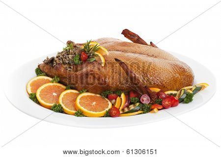 Roasted duck on a plate with salads oranges and vegetables,on a white background.