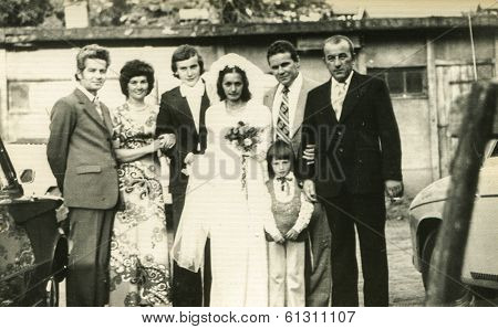 LODZ, POLAND - CIRCA 1960's: Vintage photo of newlyweds posing with their family