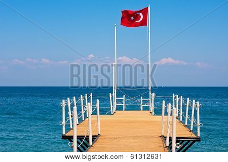 Small wooden pier and red national flag waving on the wind in Kemer - tourist resort on Mediterranean sea in Turkey.