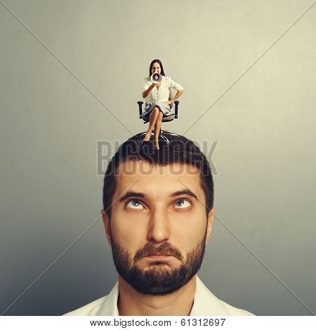 angry small woman screaming and sitting on the stupid man over grey background