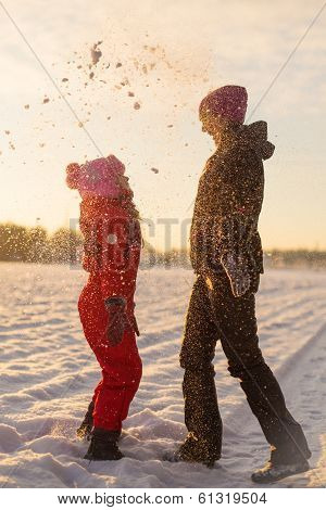 Mom and daughter playing snowballs