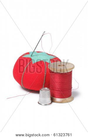 needle, thread, and pin cushion on white