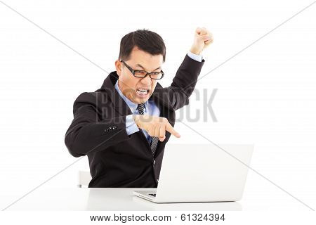 Businessman Yelling And Make A Fist With Laptop