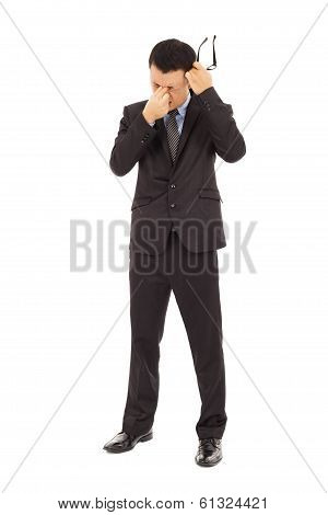 Businessman Rubbing His Eyes And Holding Glasses