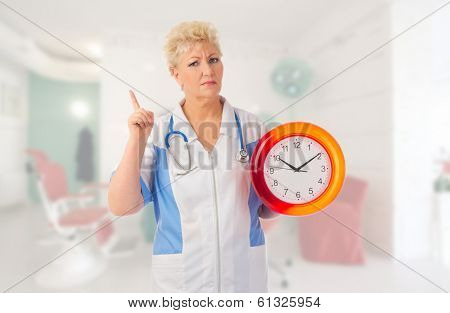 Mature nurse with clock at medical office