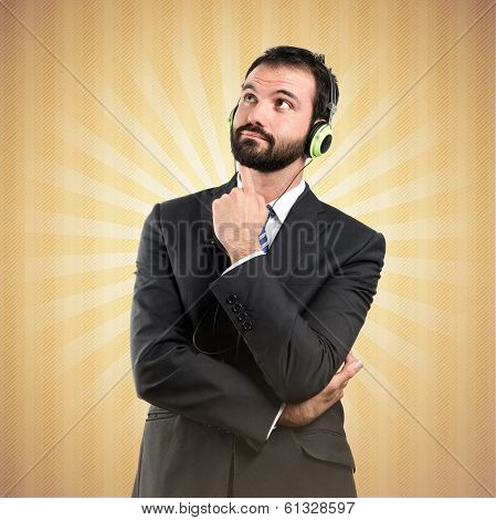 Young Businessman Listening Music Over Ocher Background