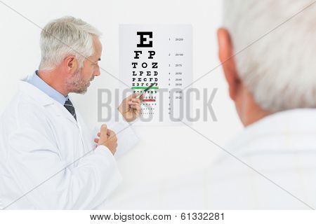 Male pediatrician ophthalmologist with senior patient pointing at eye chart in medical office