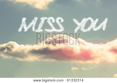The word miss you against bright blue sky with cloud