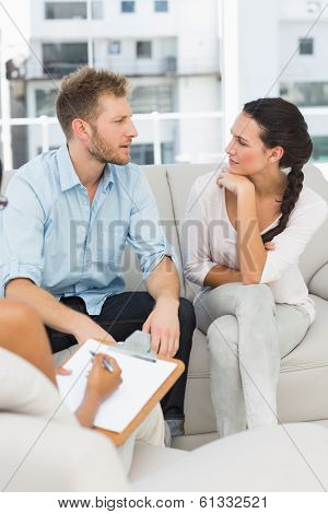 Unhappy couple talking at therapy session in therapists office